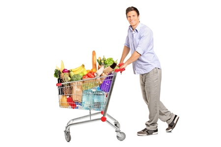 A young male pushing a shopping cart full with groceries isolated on white background
