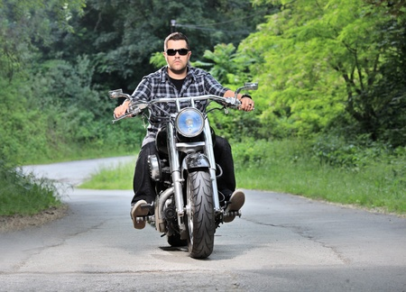 A young man riding a chopper on a road