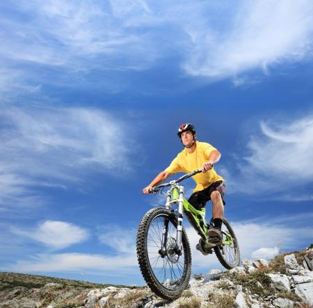 Photo pour A young man riding a mountain bike outdoor - image libre de droit