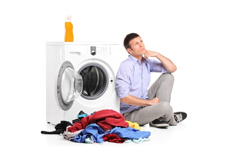 Thoughtful young male sitting next to a washing machine isolated against white background