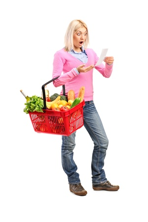 Full length portrait of a surprised woman looking at store receipt and holding a shopping basket isolated on white background