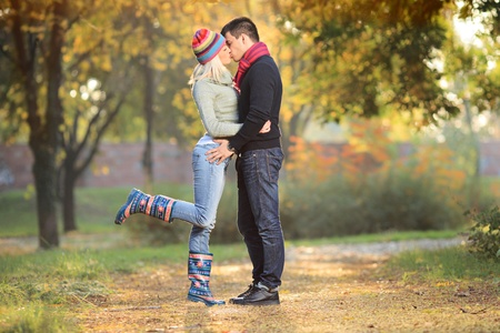 Loving couple kissing in the park in autumn