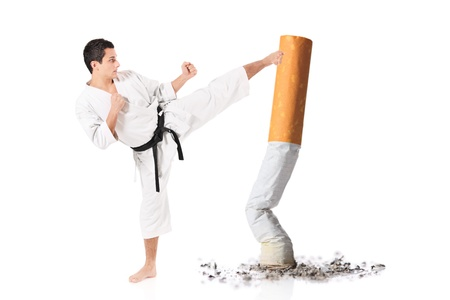 Karate man hitting a cigarette butt isolated against white background