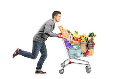 Foto de Young man running and pushing a shopping cart full with food isolated on white background - Imagen libre de derechos