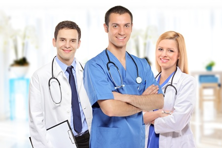 Medical team consisting of three smiling doctors inside a hospital
