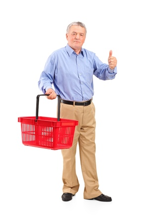 Full length portrait of a senior man holding an empty shopping basket and giving thumb up isolated on whte background