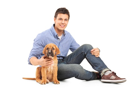 Young man with a cane corso puppy isolated on white background