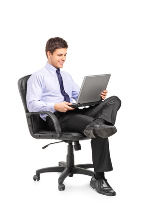 Photo for Young smiling businessman sitting in office chair and working on laptop computer isolated on white background - Royalty Free Image