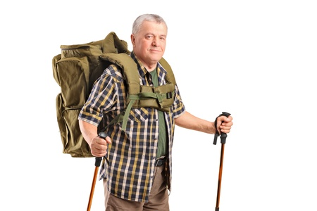 A smiling mature with backpack holding hiking poles posing isolated on white background