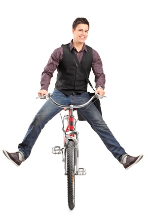 A studio shot of a young happy man riding a bike isolated on white background