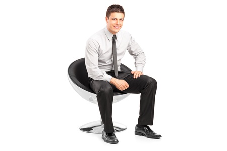 Photo for A young handsome male sitting on chair and posing isolated on white background - Royalty Free Image