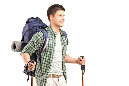 A hiker with backpack holding hiking poles and posing isolated on white background