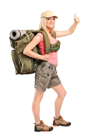 Full length portrait of a female hiker with backpack giving a thumb up isolated on white background