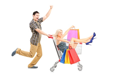 Foto de Excited person pushing a smiling woman with bags in a shopping cart isolated on white background - Imagen libre de derechos