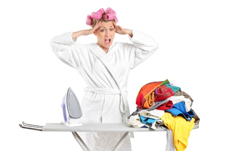 Annoyed housewife with ironing board and clothes isolated against white background