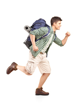 Full length portrait of a hiker with backpack running isolated on white background