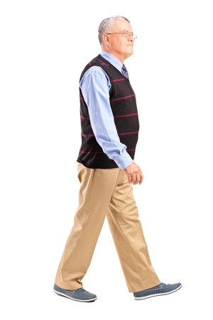 Full length portrait of a senior man walking isolated on white backgroundの写真素材