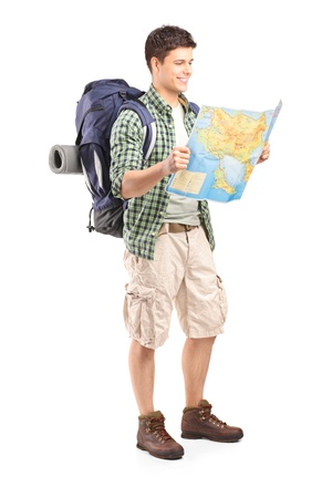 Foto de Full length portrait of male hiker looking at map isolated on white background - Imagen libre de derechos