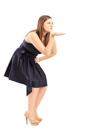 Full length portrait of a young woman blowing a kiss isolated on white background