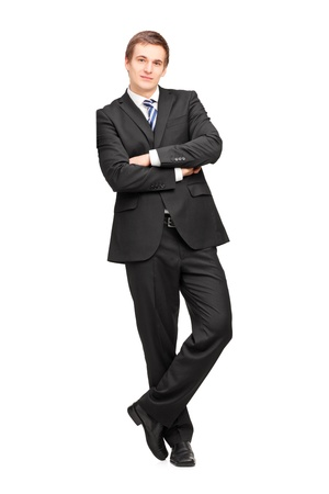 Full length portrait of a young businessman leaning against wall isolated on white backgroundの写真素材