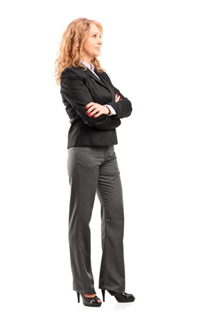 Full length portrait of a businesswoman standing with folded arms isolated on white background