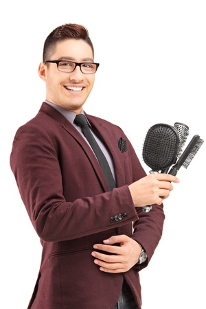 Young male hair stylist holding three hair brushes, isolated on white background