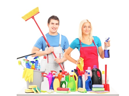 Male and female cleaners posing with cleaning supplies on a table isolated on white background