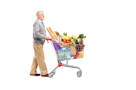 Full length potrait of a gentleman pushing a shopping cart full of groceries isolated on white background