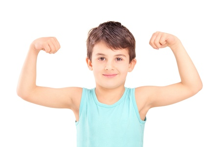 A kid showing his muscles isolated on white background