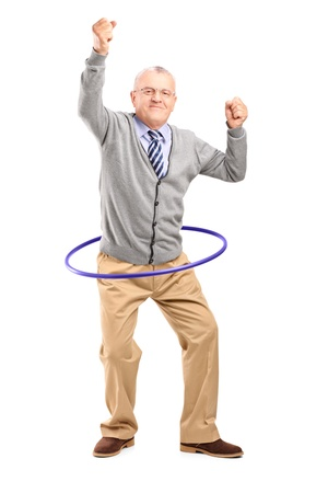 Full length portrait of a mature gentleman dancing with a hula hoop isolated on white background