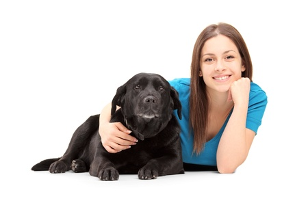 A young female lying and posing with a black dog isolated on white background