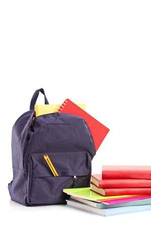 Studio shot of a school backpack with books and notebooks, isolated on white background