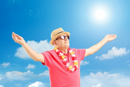 Happy mature man on a vacation spreading his arms on a sunny day