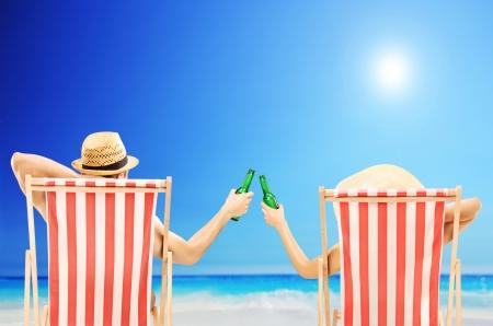 Foto de Man and woman relaxing on a beach and cheering with beer bottles - Imagen libre de derechos