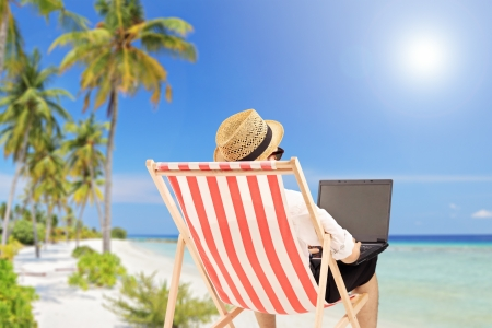 Photo for Young man on an outdoor chair working on a laptop, on a tropical beach - Royalty Free Image
