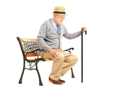 Senior man with a cane sitting on a bench isolated on white background