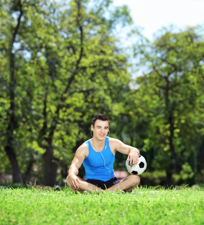 Young smiling male athlete sitting down on a green grass with soccer ball in a park, shot with a tilt and shift lens