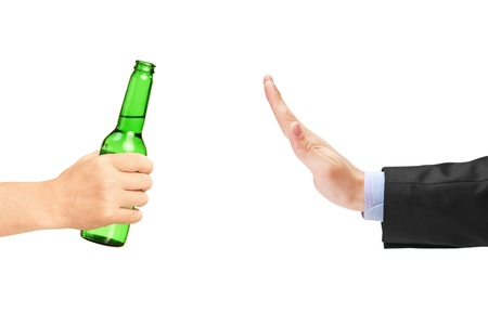Man in suit refusing a bottle of beer isolated on white background