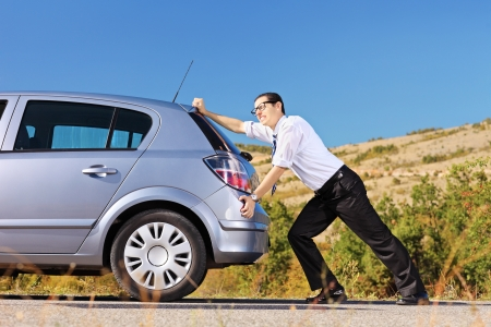 Young man pushing his broken car or a car out of gas, on a sunny day