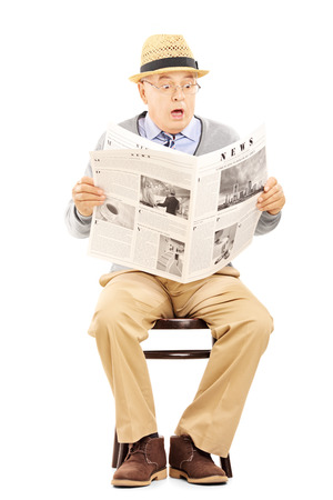 Senior gentleman in shock on a wooden chair reading a newspaper isolated on white background