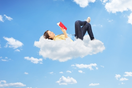 Young relaxed female reading a novel and lying on clouds