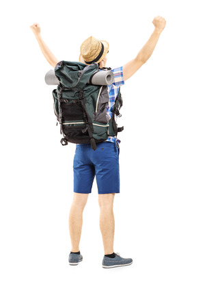Full length portrait of a male hiker with raised hands gesturing happiness isolated on white background