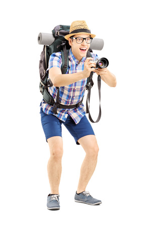 Full length portrait of a male tourist with backpack taking a picture with the camera isolated on white background