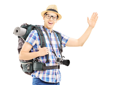 Male tourist with backpack waving with his hand isolated on white background