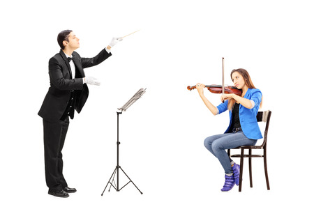 Male orchestra conductor directing a female playing violin isolated against white background