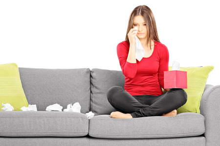 Sad young female sitting on a couch and wiping her eyes from crying isolated on white background
