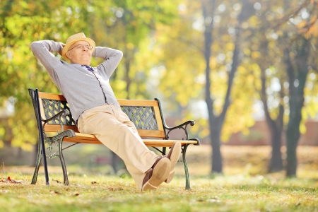 Senior gentleman sitting on a wooden bench and relaxing in a park