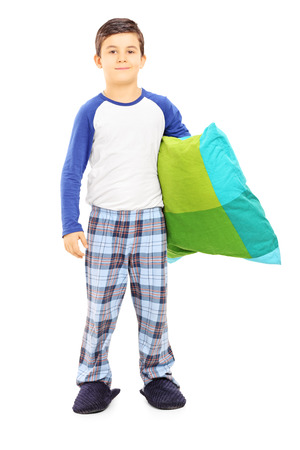 Full length portrait of boy in pajamas holding a pillow isolated on white background