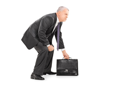 Mature businessman holding a suitcase and standing in sumo wrestling stance isolated on white background