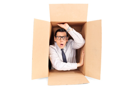 Photo pour Young businessman trapped in a box isolated on white background - image libre de droit